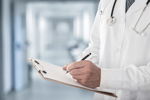 Close up of male doctor holding clipboard filling up medical form standing in hospital